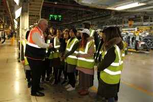 students in awe of man from jaguar also in high vis