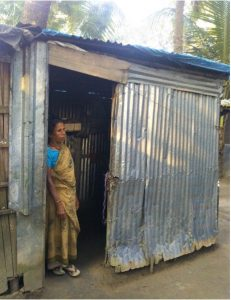 Woman in a sari leans against the door of her house. It is a one story metal building